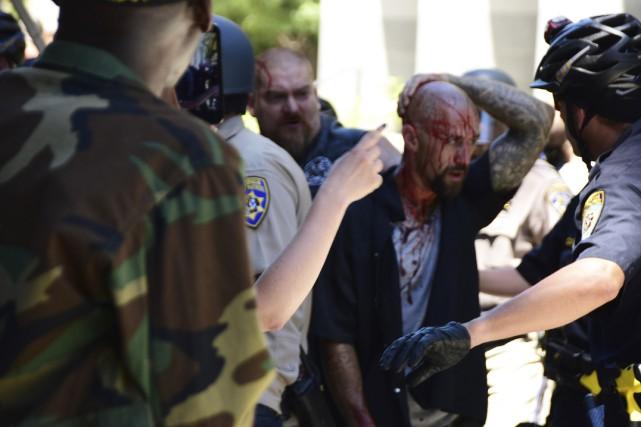 La police escorte un blessé en retrait du... (AP, Steven Styles)