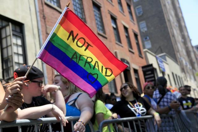 Une femme tient un drapeau de la fierté... (PHOTO SETH WENIG, AP)