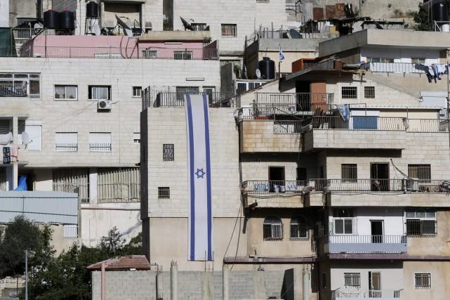 Des drapeaux israéliens sont vus sur des immeubles... (PHOTO  AHMAD GHARABLI, ARCHIVES AFP)