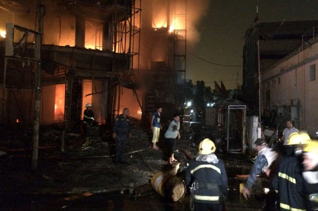 Pompiers et civils s'affairaient à éteindre les incendies... (Photo Hadi Mizban, AP)
