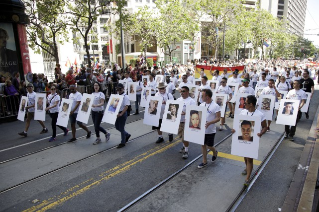Des marcheurs paradent avec les photos des victimes... (Associated Press, Marcio Jose Sanchez)