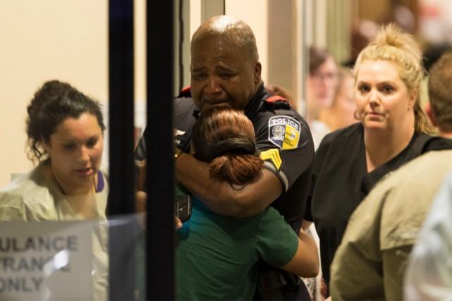 Un policier de Dallas est réconforté à la... (AP)