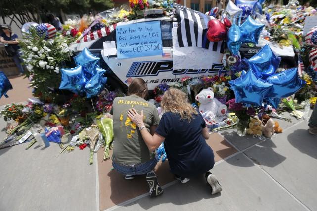 Des gens déposent des fleurs devant le poste... (Associated Press, Gerald Herbert)