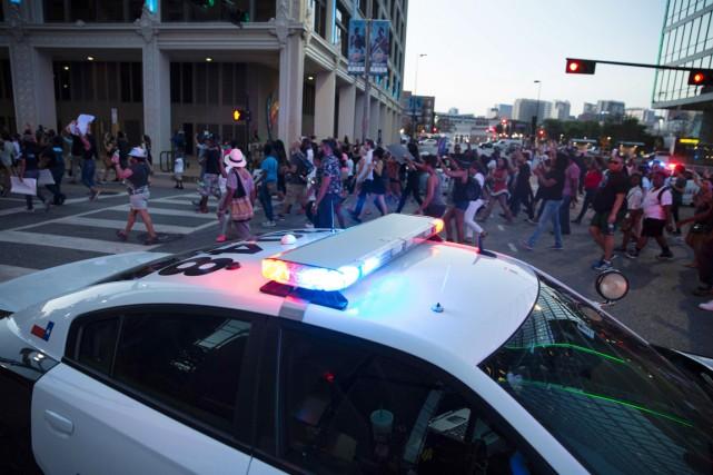 Une voiture de police surveille les manifestants rassemblés... (PHOTO LAURA BUCKMAN, AFP)