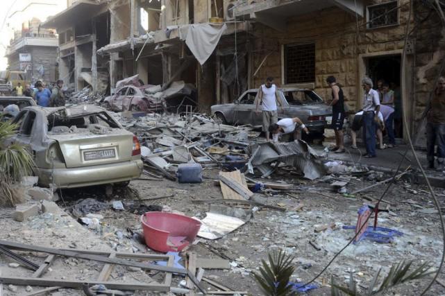 Des gens constatent les dégâts causés par des... (PHOTO GEORGE OURFALIAN, AFP)