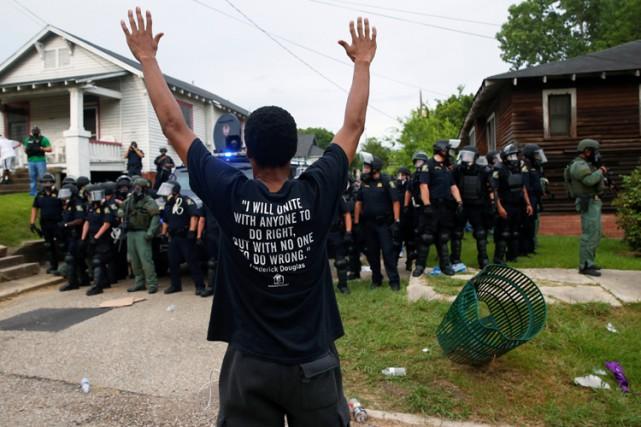 Un manifestant lève les bras devant des policiers... (PHOTO REUTERS)