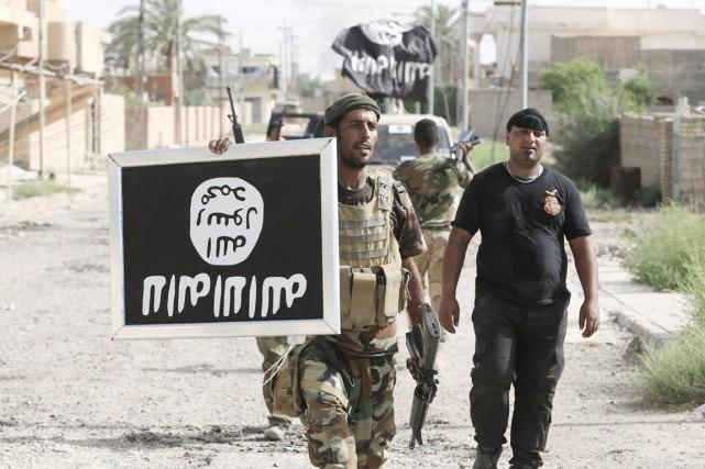 Un combattant chiites irakien tient une affiche à... (photo archives REUTERS/stringer)
