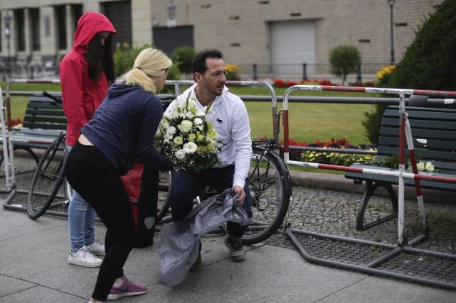 Des gens déposent des fleurs devant l'ambassade française... (AP)