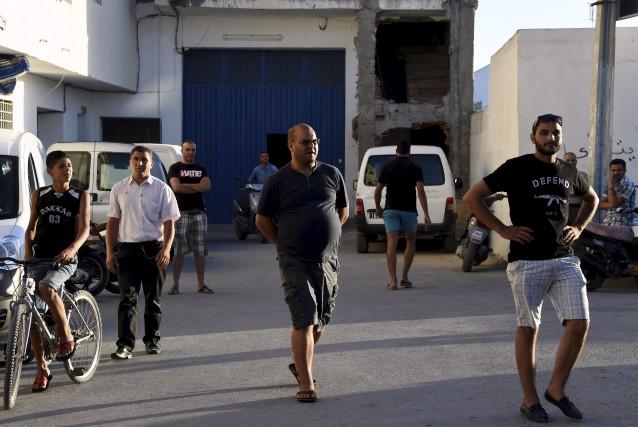 Des voisins se tiennent près du domicile familial... (AFP, FETHI BELAID)