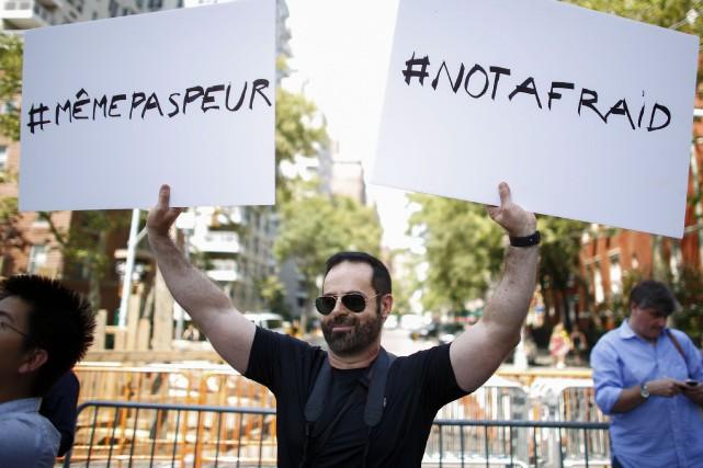Un homme tient deux pancartes lors d'une vigile... (AFP)