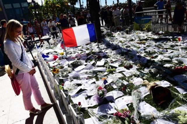 Une femme pleure devant le mémorial improvisé en... (PHOTO GIUSEPPE CACACE, AGENCE FRANCE-PRESSE)