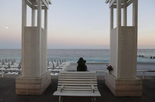 Une femme est assise sur un blanc près... (AFP)