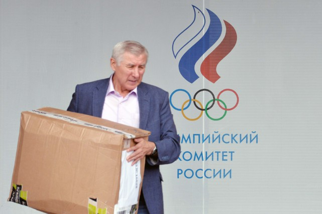 Un homme est vu transportant une boîte de... (photo Natalia KOLESNIKOVA, AFP)