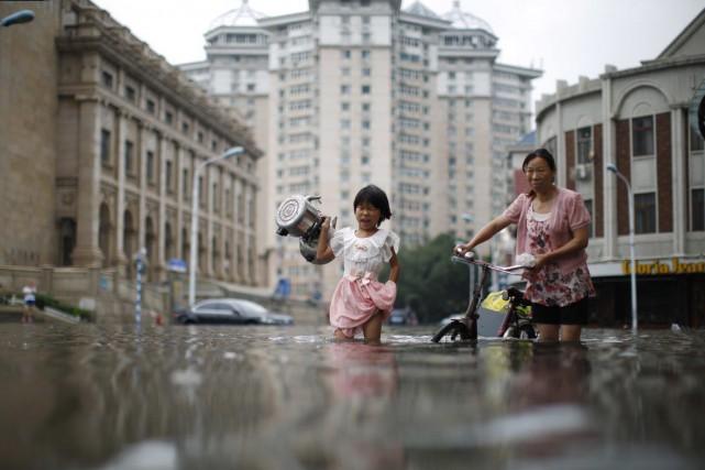 Une enfant et une femme traversent une rue... (Photo AP)