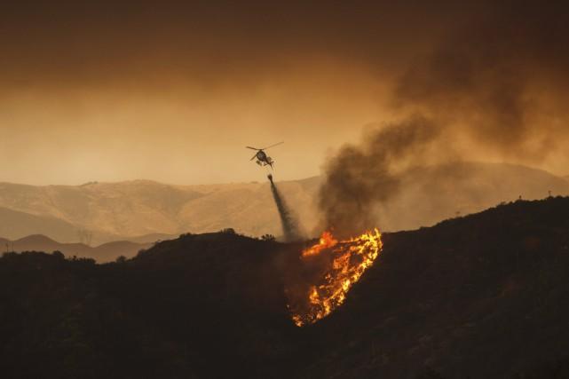 Un hélicoptère combat les flammes près de Santa... (AFP, David Mcnew)