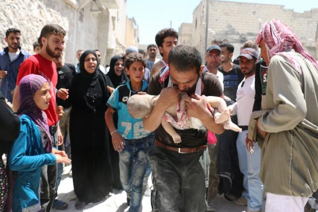 Un homme transporte son bébé sorti des décombres,... (PHOTO AFP)