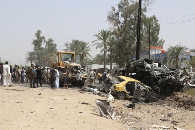 Des Irakiens inspectent les dommages après un attentat-suicide... (AFP)