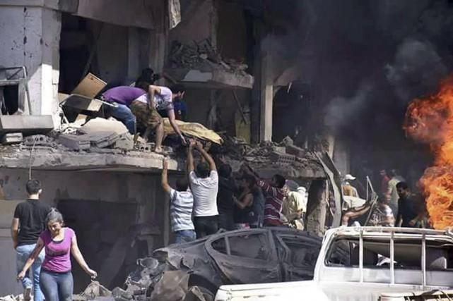 Les secouristes retirent des corps des débris à... (AP)