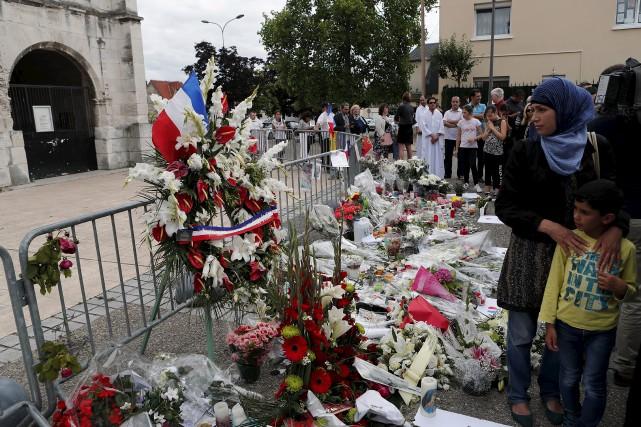 Des gens se recueillent au mémorial aménagé devant... (AP, François Mori)