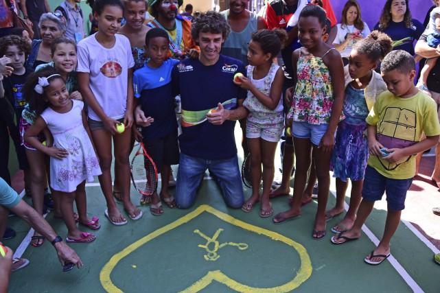 Gustavo Kuerten avec des jeunes dans la favela... (AFP, Tasso Marcelo)