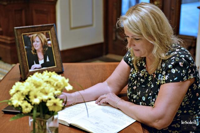 La ministre Lise Thériault a signé le registre... (Le Soleil, Pascal Ratthé)
