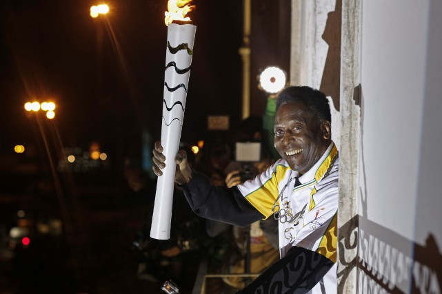 Pelé avec la flamme olympique... (Photo Andre Luiz Mello, AFP)
