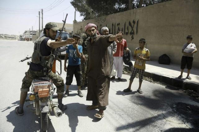Des soldats desForces démocratiques syrienne indiquent aux habitants... (PHOTO DELIL SOULEIMAN, AGENCE FRANCE-PRESSE)