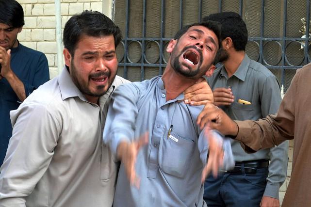 Deux hommes pleurent le décès des victimes de... (PHOTO BANARAS KHAN, AFP)