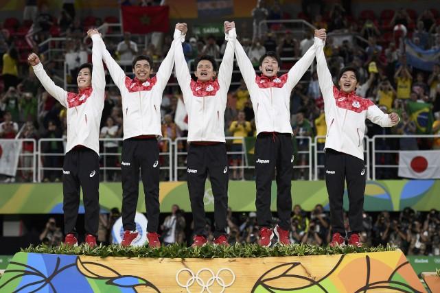 Les gymnastes japonais célèbrent sur le podium après... (Photo Dylan Martinez, REUTERS)