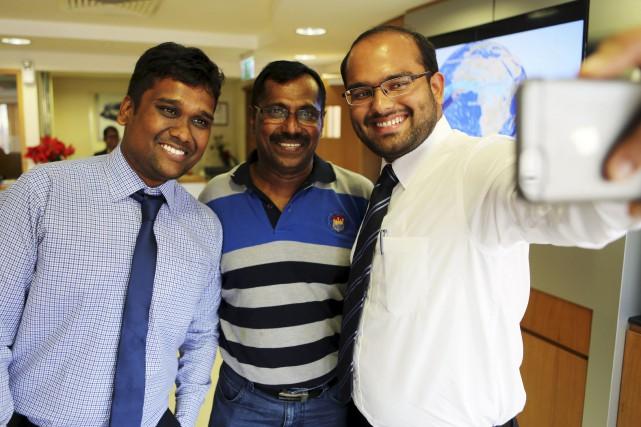 Mohamed Basheer (au centre) se prête au jeu... (AP, Jon Gambrell)