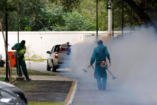 Des employés répandent de l'insecticide près des installations... (PHOTO CHRIS HELGREN, REUTERS)