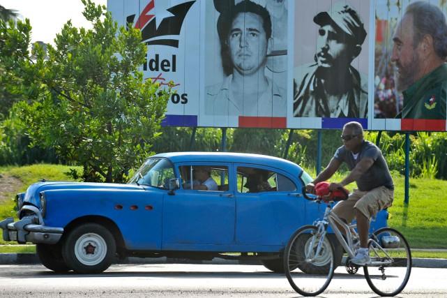 Une affiche avec trois photos de Fidel Castro:... (PHOTO AFP)