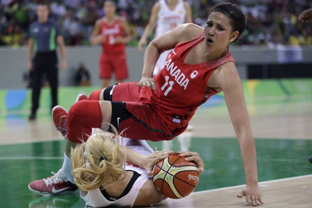 La Canadienne Natalie Achonwa chute sur l'Espagnole Laura... (AP, Carlos Osorio)