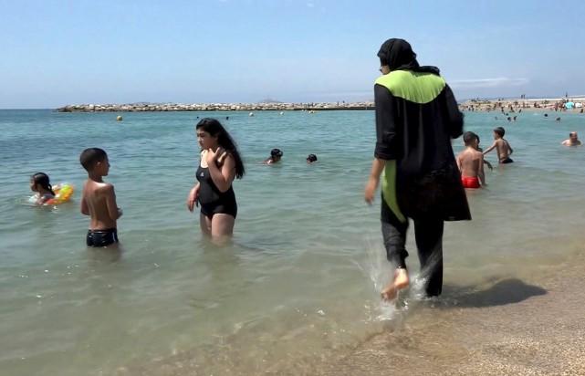 Alors que les baigneuses portant le burkini se... (La Presse Canadienne)