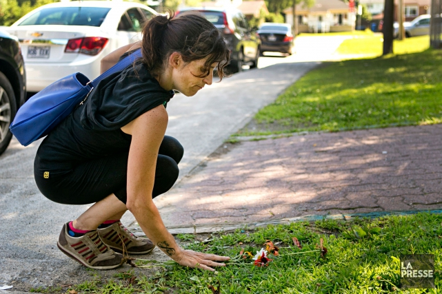 Une femme dépose des fleurs au pied de... (PHOTO DAVID BOILY, LA PRESSE)