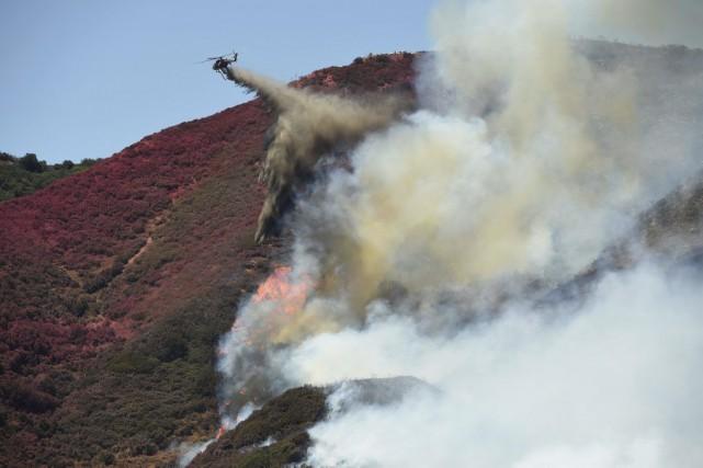 Un hélicoptère laisse tomber l'eau contenue dans son... (PHOTO JOSH EDELSON, AFP)