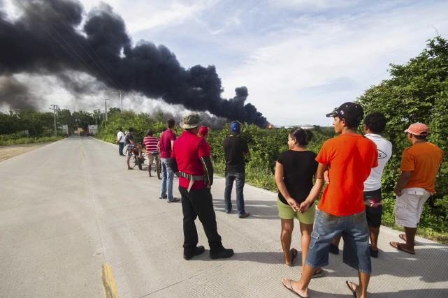Des résidants observent la fumée, au loin. Le... (AFP, Alfredo Zuniga)