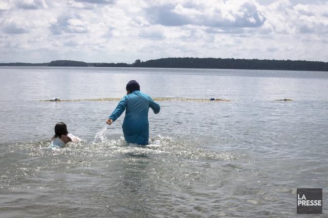 Une femme vetu d'un burkini se baigne en... (Olivier Pontbriand, La Presse)