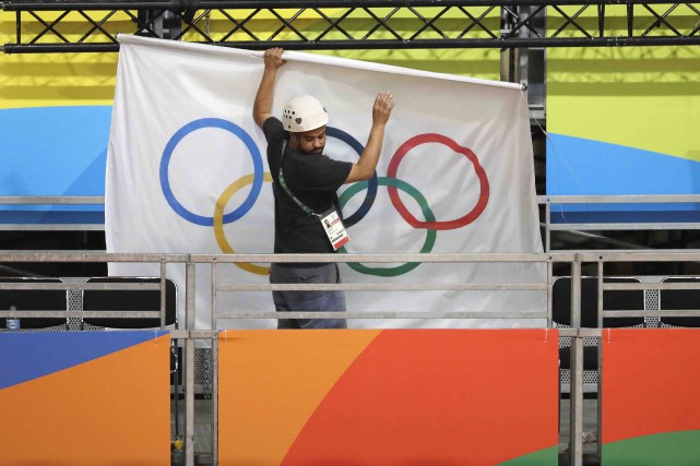 Un ouvrier décroche le drapeau olympique de la... (AP, Mark Humphrey)