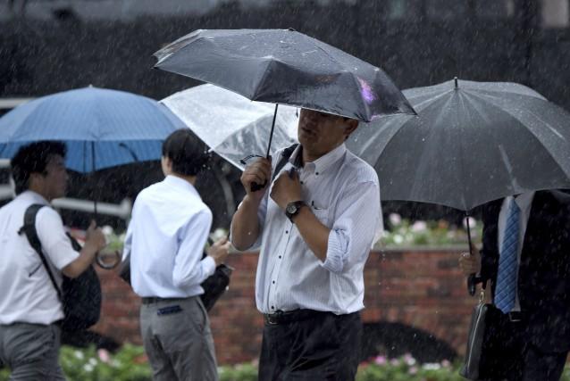 Des hommes d'affaires tentent de se protéger de... (AFP, Toru Yamanaka)