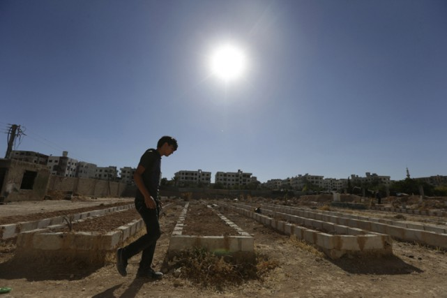Un homme marche près de fosses communesoù sont... (PHOTO ARCHIVES REUTERS)