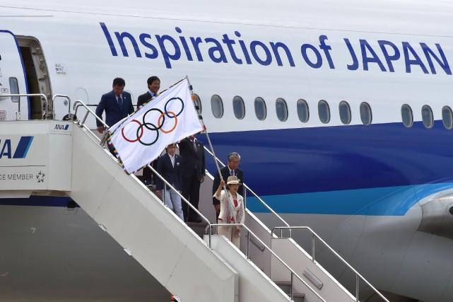 La gouverneure de Tokyo, Yuriko Koike,brandit le drapeau... (Photo Kazuhiro Nogi, AFP)