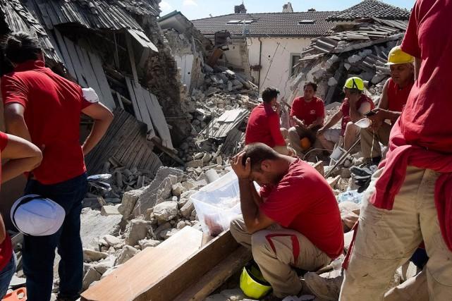 Des secouristes prennent une pause à Amatrice, ville... (Photo Emilio Fraile, AP)