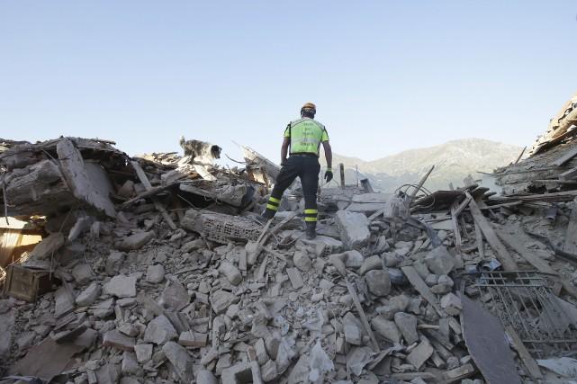 Un secroutiste surplombe le cente-ville d'Amatrice.... (AP)