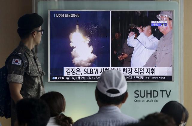 Des soldats regardent le lancement d'un missile nord-coréen... (Associated Press)