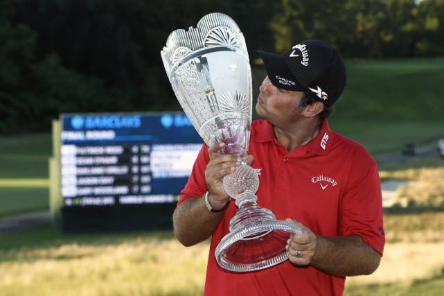 Patrick Reed embrasse le trophée après sa victoire... (Kathy Kmonicek, Associated Press)