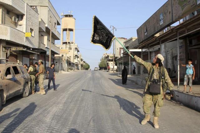 Un combattant du Jound al-Aqsa lève un drapeau... (PHOTO OMAR HAJ KADOUR, AGENCE FRANCE-PRESSE)