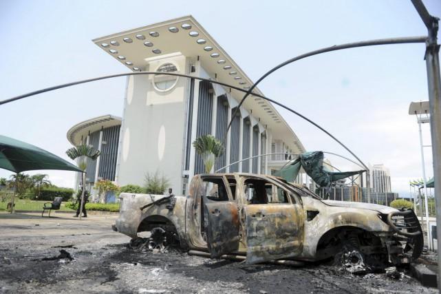 Une voiture incendiée se trouve à proximité d'un... (Photo Joel Bouopda, AP)