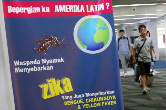 Des voyageurs arrivent à l'aéroport international Soekarno-Hatta de... (Tatan Syuflana, AP)