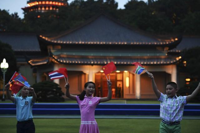 Des enfants agitent les drapeaux des nations du... (AFP)